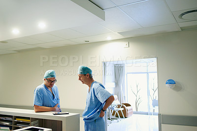 Buy stock photo Cropped shot of two male doctors looking at a tablet while standing in a hospital