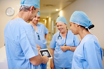 Buy stock photo Cropped shot of a team of doctors looking at a tablet displaying an MRI scan while standing in a hospital