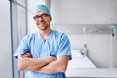 Buy stock photo Cropped portrait of a handsome young male doctor standing with his arms folded in the hospital