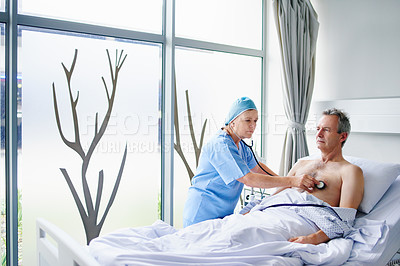 Buy stock photo Cropped shot of a mature female doctor checking her male patient's heartbeat in his hospital bed