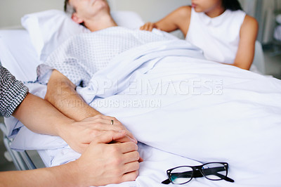 Buy stock photo Closeup shot of an unrecognizable man's hand holding his father's in comfort at the hospital