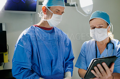 Buy stock photo Cropped shot of two doctors getting ready for surgery in the operating room