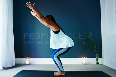 Buy stock photo Shot of a beautiful young woman practising yoga at home