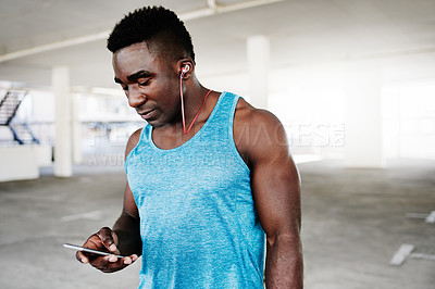 Buy stock photo Shot of a sporty young man using a mobile phone while working out in an underground parking lot
