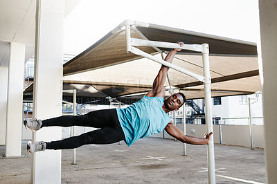 Buy stock photo Shot of a handsome and sporty young man working out with a pole against a city background