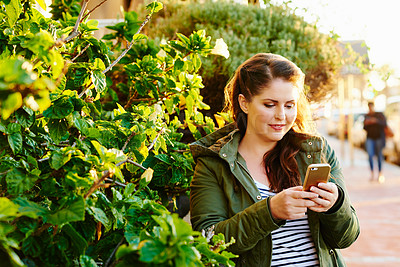 Buy stock photo Cropped shot of a beautiful young woman using a cellphone and spending the day outside