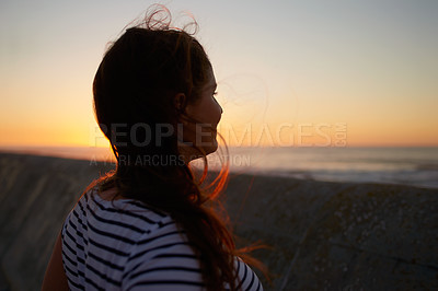 Buy stock photo Cropped shot of an unrecognizable woman looking at the sunset on the promenade at the beach