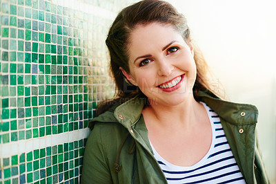 Buy stock photo Portrait of a beautiful young woman posing against a green wall outside