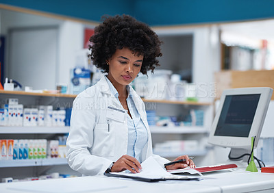 Buy stock photo Shot of a young pharmacist working on a computer in a pharmacy