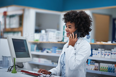 Buy stock photo Shot of a young pharmacist talking on a cellphone while working in a pharmacy
