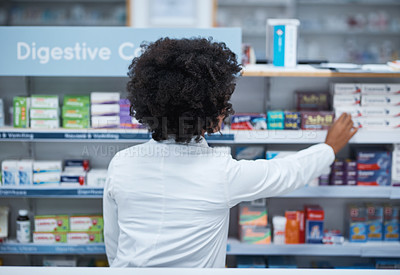 Buy stock photo Rearview shot of a young pharmacist looking at medication on a shelf in a chemist