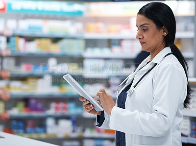 Buy stock photo Shot of a mature pharmacist working on a digital tablet in a chemist