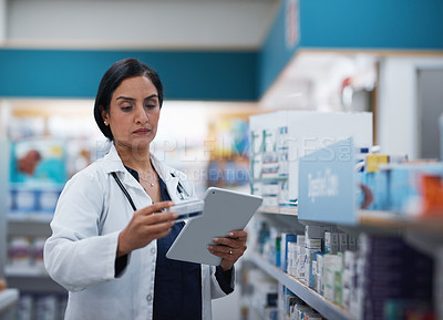 Buy stock photo Shot of a mature pharmacist using a digital tablet while looking at medication in a chemist