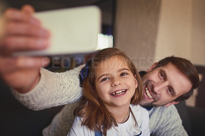Buy stock photo Cropped shot of a handsome man and his adorable young daughter taking selfies on the sofa at home