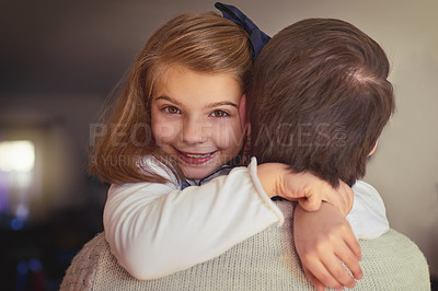 Buy stock photo Cropped portrait of an adorable little girl embracing her dad in their home