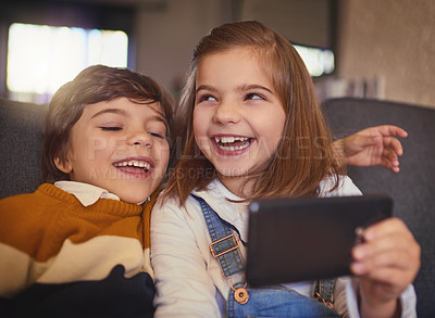 Buy stock photo Cropped shot of an adorable little girl and her younger brother taking selfies while sitting on the sofa at home