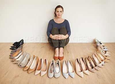Buy stock photo Full length portrait of an attractive young woman sitting on a wooden floor surrounded by high heels
