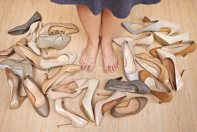 Buy stock photo High angle shot of an unrecognizable woman standing on a wooden floor surrounded by high heels
