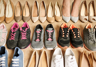 Buy stock photo High angle shot of an unrecognizable woman trying on shoes one by one as their lined up on a wooden floor