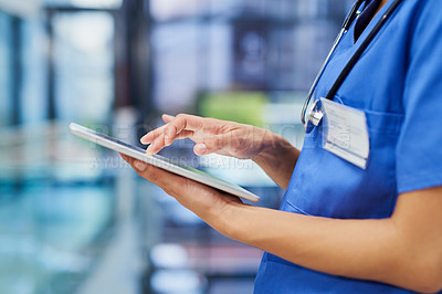 Buy stock photo Cropped shot of an unrecognizable female nurse using a tablet while standing in the hospital