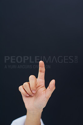 Buy stock photo Cropped shot of an unrecognizable female nurse's hand while using a touchscreen interface while standing against a black background