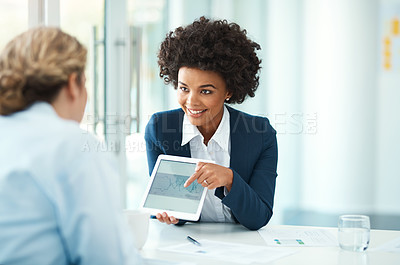 Buy stock photo Shot of a businesswoman referring to something on a digital tablet