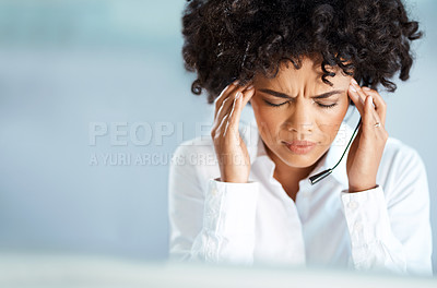 Buy stock photo Shot of a young call centre agent suffering with a headache while working in an office