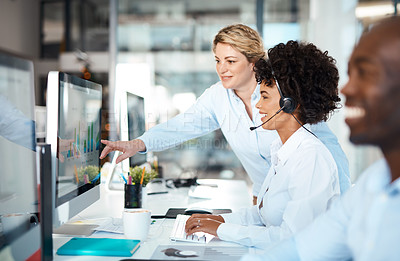 Buy stock photo Shot of a young businesswoman assisting a colleague in a call centre