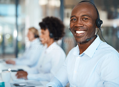 Buy stock photo Portrait of a young call centre agent working in an office with his colleagues in the background