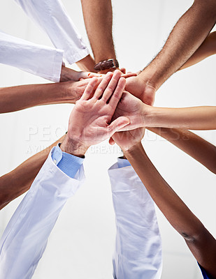 Buy stock photo Low angle shot of a diverse team of doctors joining their hands together in a hospital