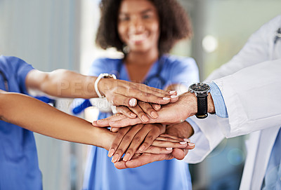 Buy stock photo Closeup shot of a diverse team of doctors joining their hands together in a hospital