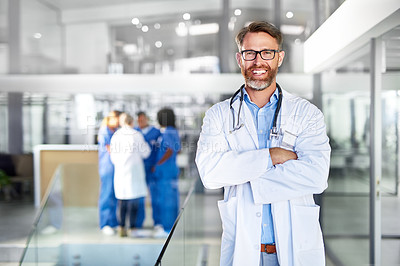 Buy stock photo Portrait of a confident mature doctor working in a hospital with his colleagues in the background