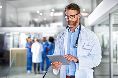 Buy stock photo Shot of a mature doctor using a digital tablet in a hospital with his colleagues in the background