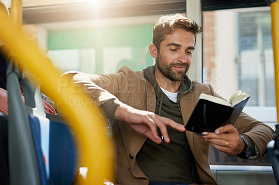 Buy stock photo Cropped shot of a handsome young man reading a book during his morning bus commute