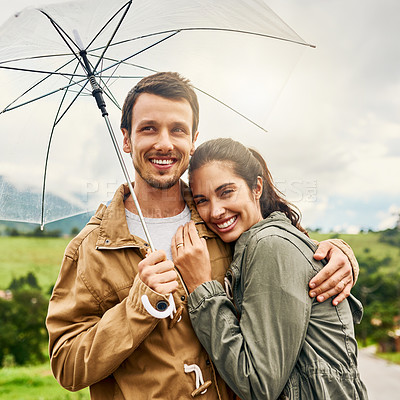 Buy stock photo Cropped shot of a loving couple standing outside with an umbrella