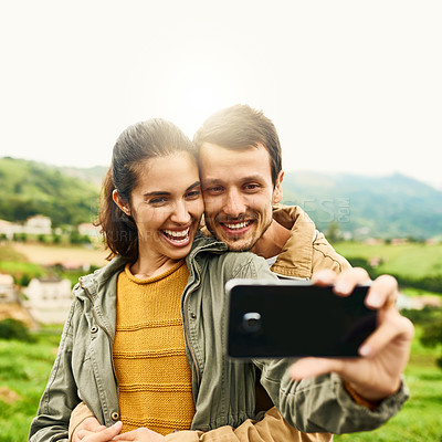 Buy stock photo Cropped shot of a loving couple taking a selfie outdoors