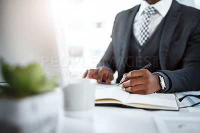 Buy stock photo Cropped shot of a businessman using a computer and writing notes at his desk in a modern office