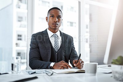 Buy stock photo Shot of a young businessman writing notes and looking thoughtful at his desk in a modern office