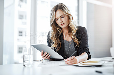 Buy stock photo Shot of a young businesswoman using a digital tablet and writing notes at her desk in a modern office