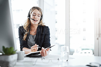 Buy stock photo Shot of a young woman using a headset and writing in a notebook at her desk in a modern office