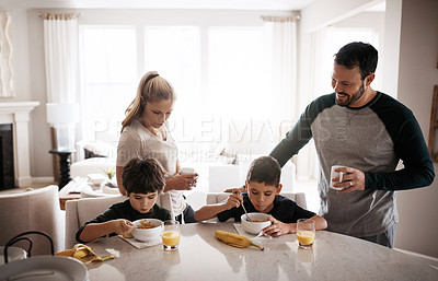 Buy stock photo Shot of two adorable brothers having breakfast together with their parents at home