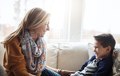 Buy stock photo Shot of an adorable little boy bonding with his mother on the sofa at home