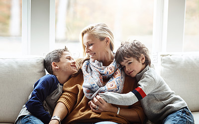 Buy stock photo Shot of two adorable little boys relaxing with their mother on the sofa at home