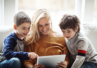 Buy stock photo Shot of two adorable brothers using a digital tablet together with their mother while relaxing on the sofa at home