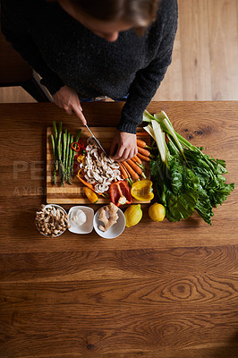 Buy stock photo High angle shot of a woman cutting a variety of healthy vegetables on a chopping board