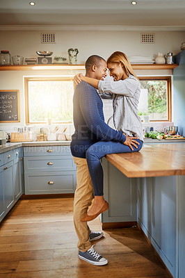 Buy stock photo Shot of an affectionate couple in their kitchen at home