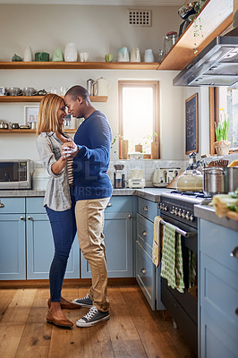 Buy stock photo Shot of a young couple dancing in their kitchen at home