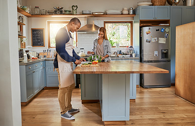 Buy stock photo Shot of a young couple cooking in the kitchen