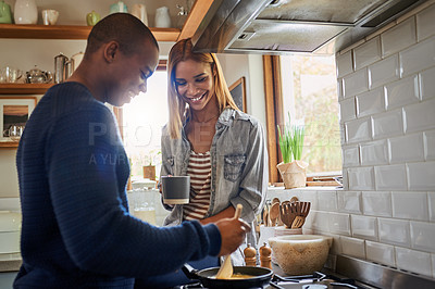 Buy stock photo Shot of a woman keeping her boyfriend company while he cooks