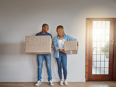 Buy stock photo Shot of a young couple carrying cardboard boxes in their new house